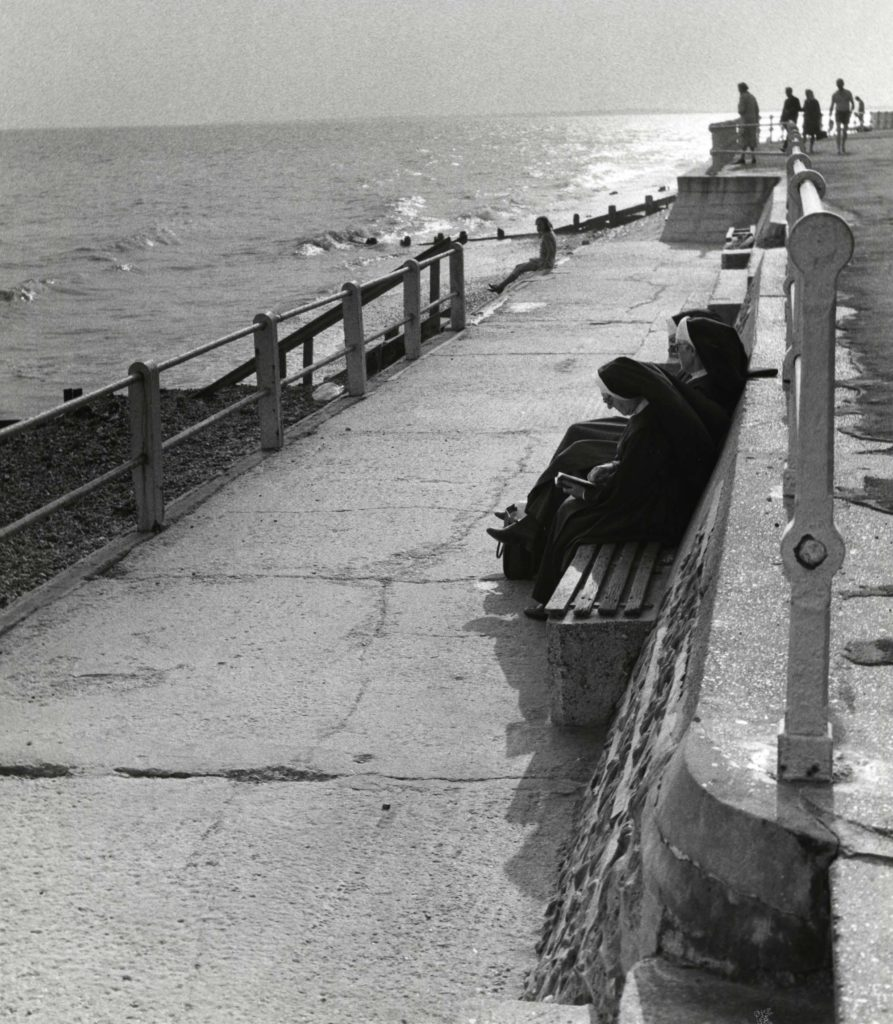 a photo of two nuns sitting on a pier with a broiling sea beyond them