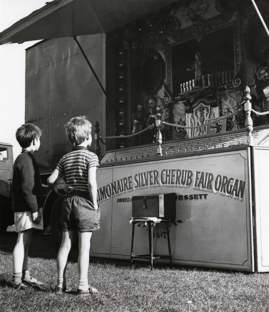 a black and white photo of two young boys in shorts looking at a steam driven pipe organ