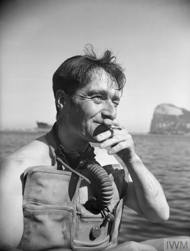 a black and white photo of a man with breathing apparatus around his neck smoking a cigarette