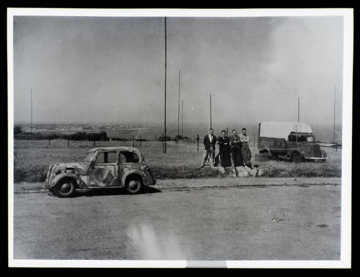 a black and white photo of a group of men standing by an aerial mast and a camouflaged car