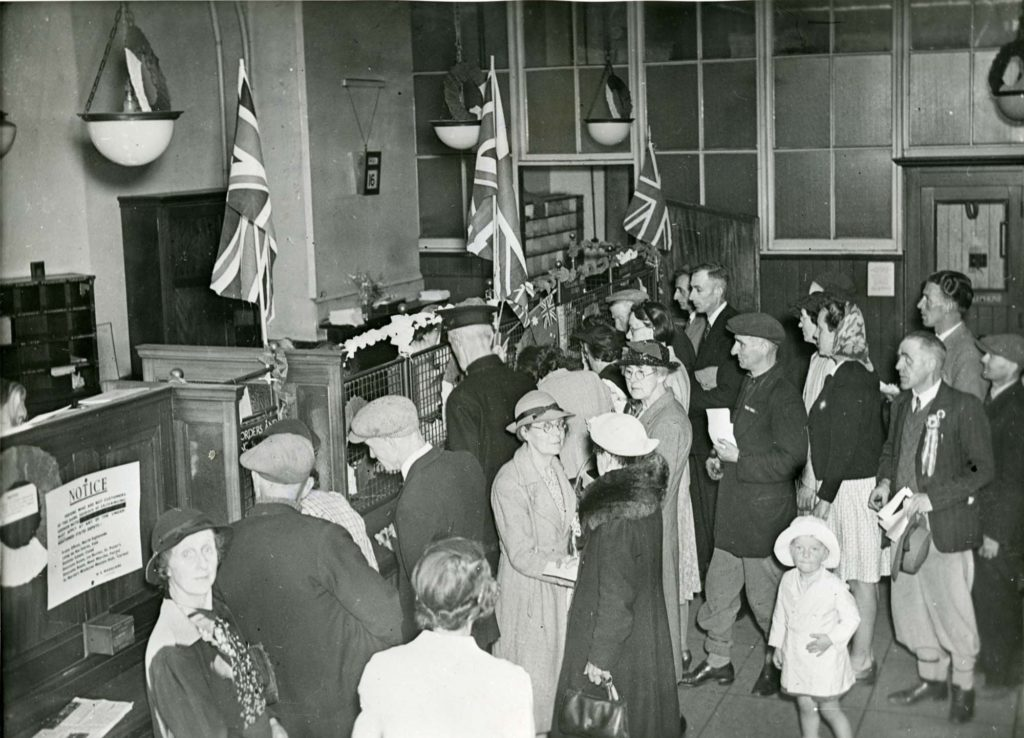 a black and white photo of a post office counter crowded with people