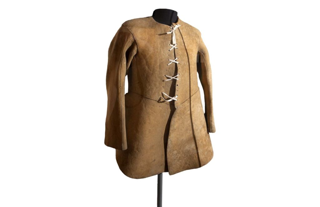 a photo of a long sleeved collarless tan leather coat with string fastening to the front