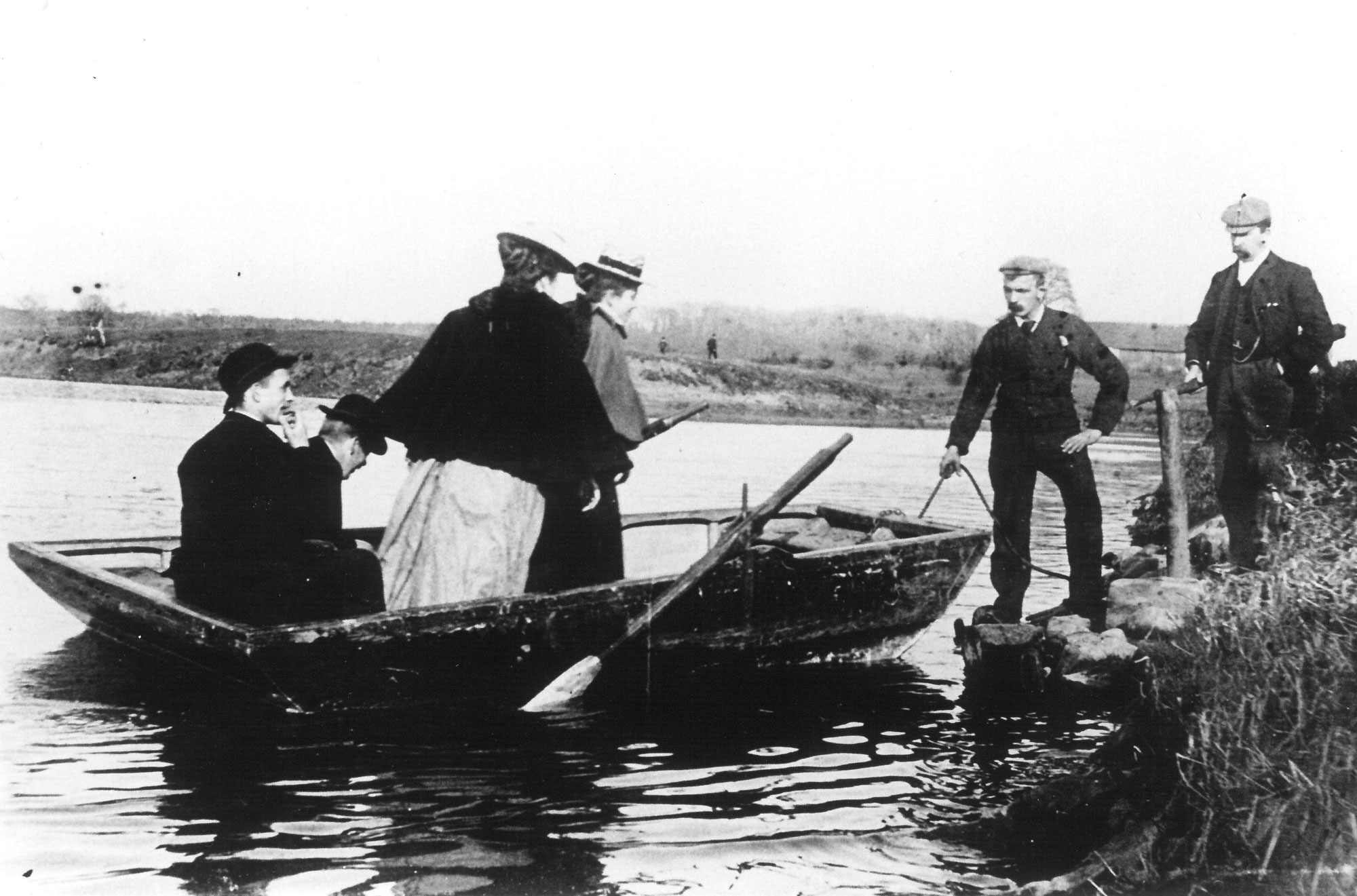 an old photo of people disembarking from a boat on a river bank