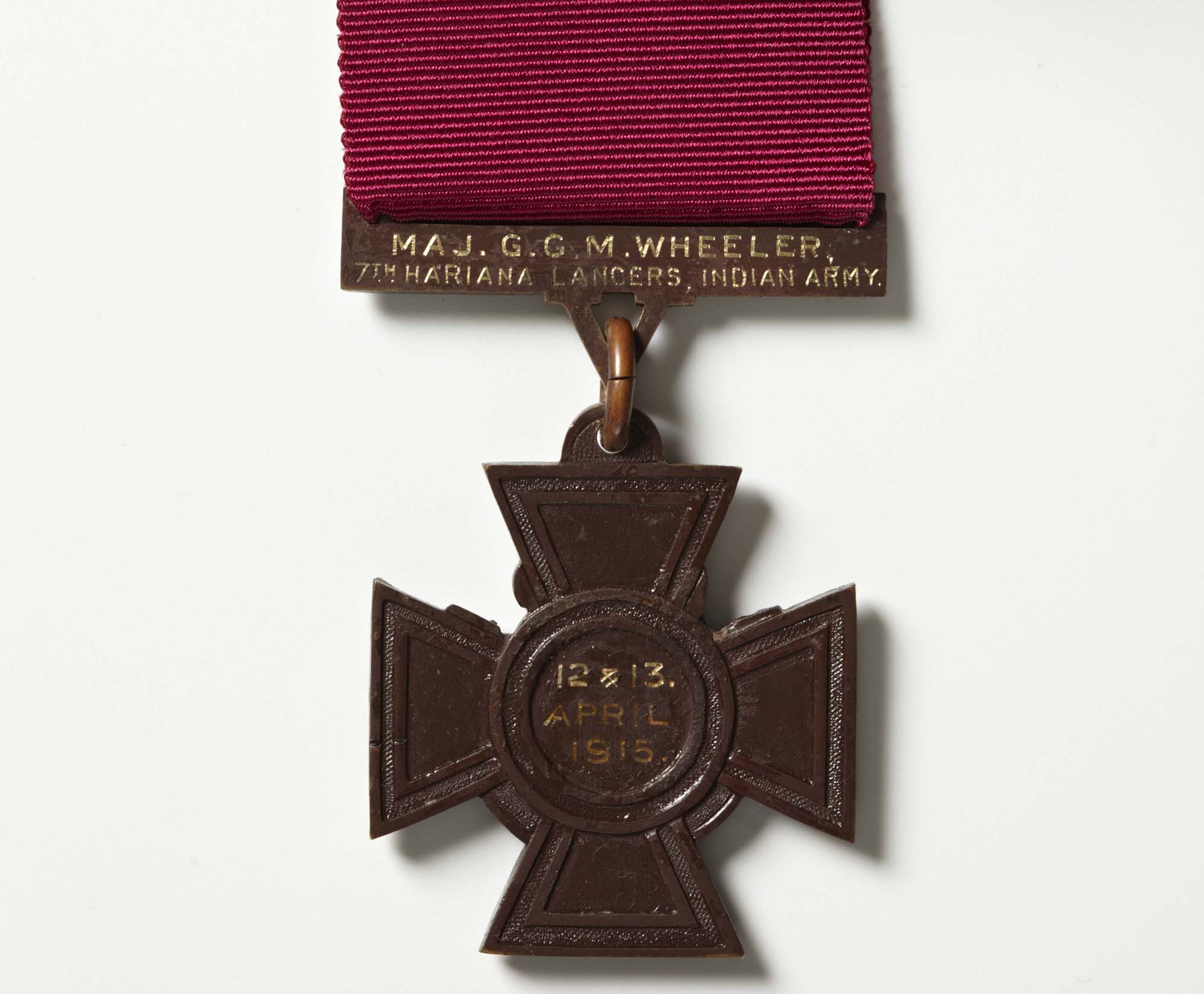a photo of a bronze cross with a dark purple medal ribbon and the date 12 & 13 April 1915.