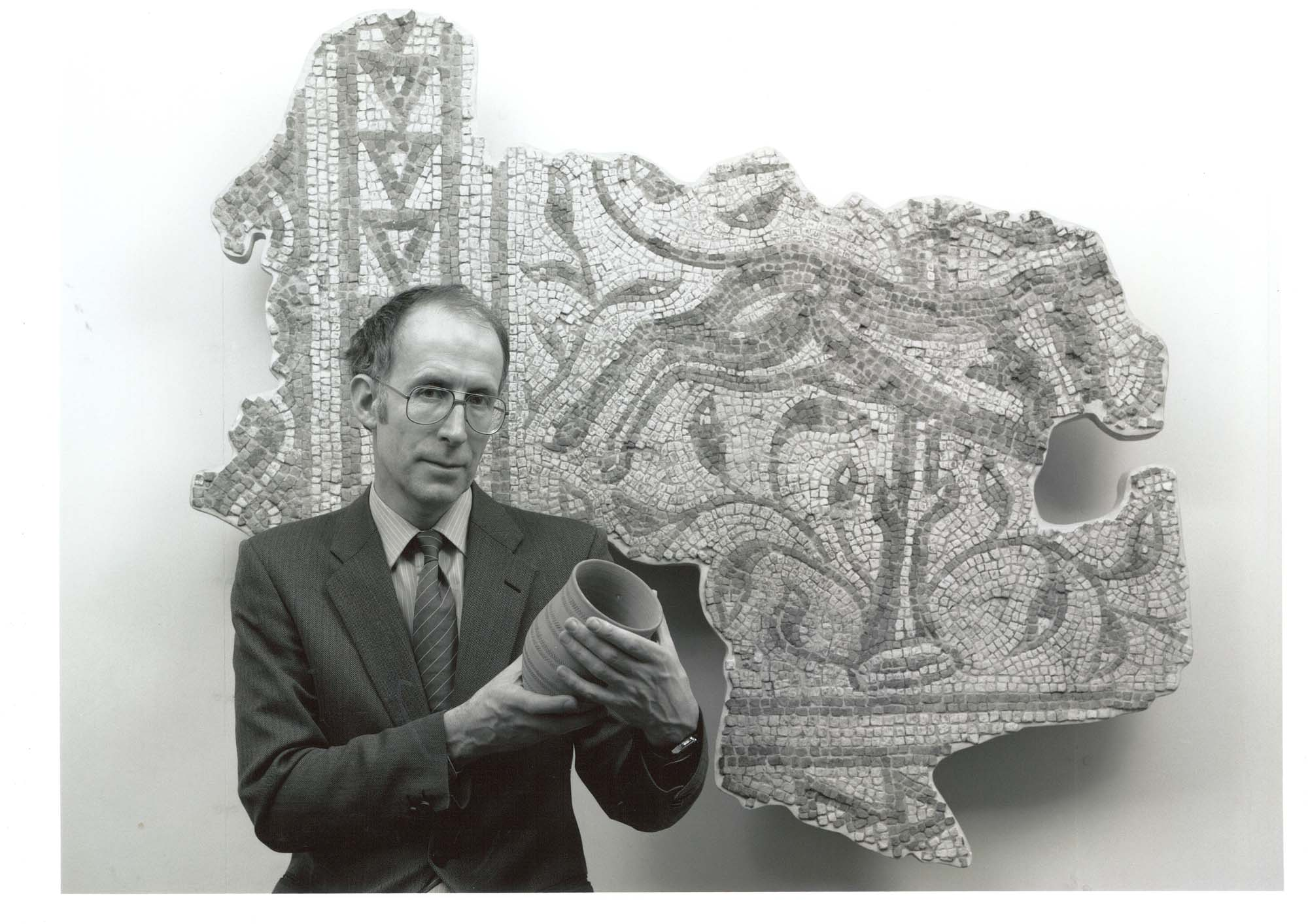 a black and white photo of a man holding a beaker in front of a wall mounted mosaic