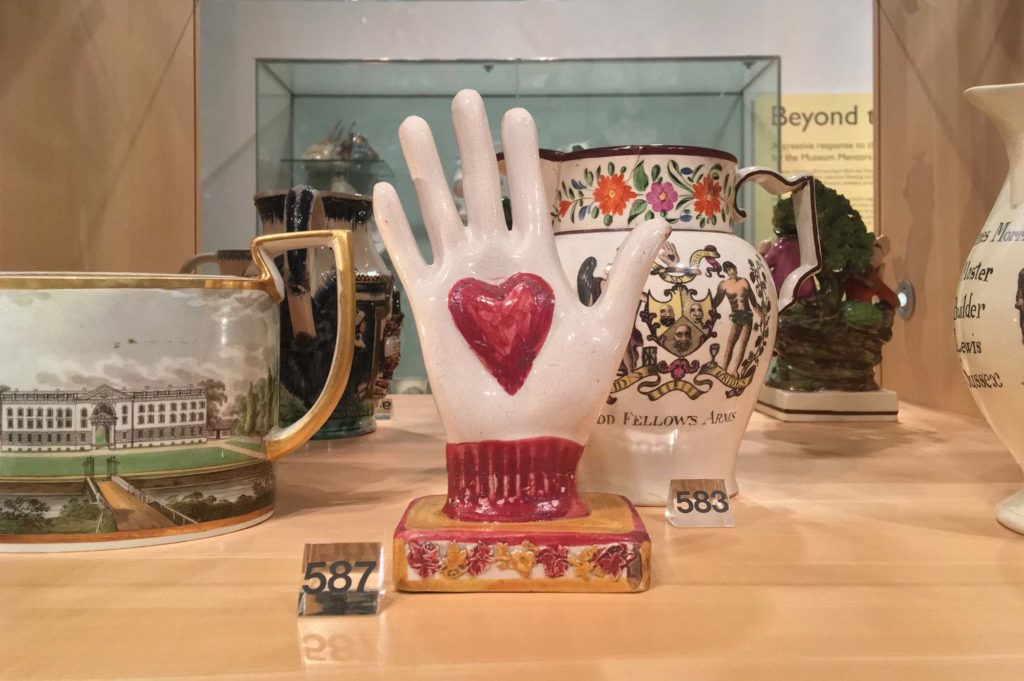 a photo of a ceramic hand with a heart motif in a display case
