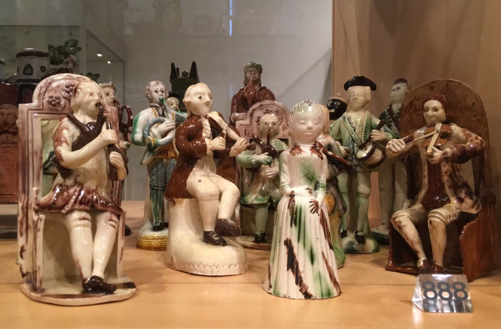 a photo of a series of small musical figurines in a display case