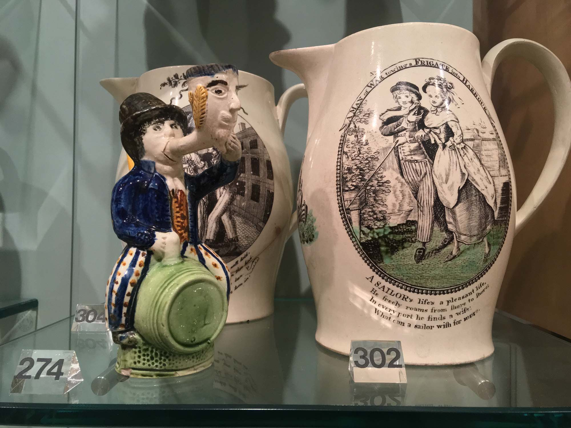 a close up of a series of pots and ceramics showing eighteenth century sailors