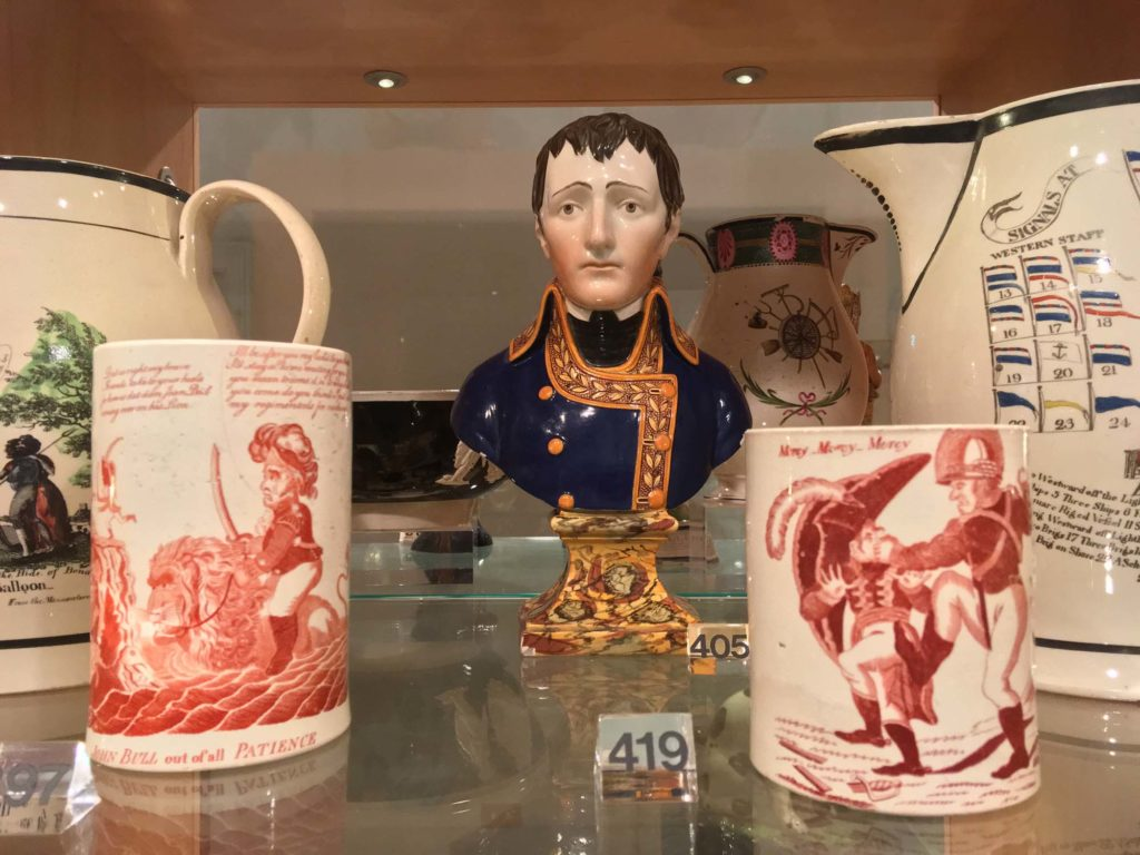 a photo of a display of two ceramic mugs and a bust