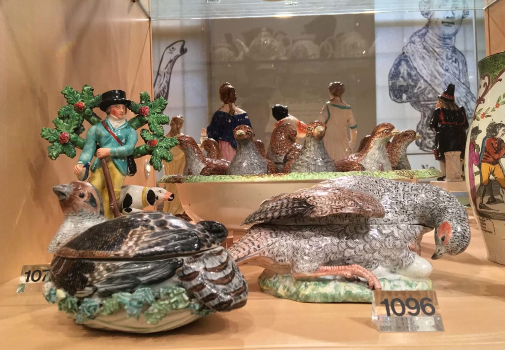 a photo of a display case with bird like ceramics in it