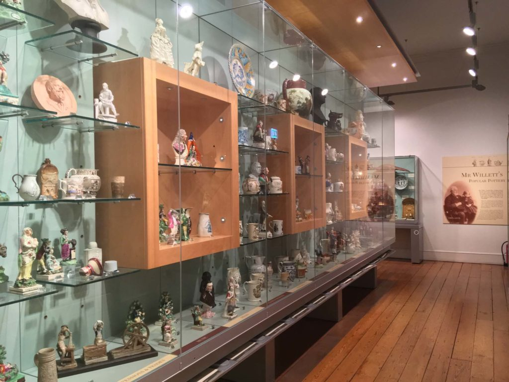 a long view of a gallery with display cases full of ceramics