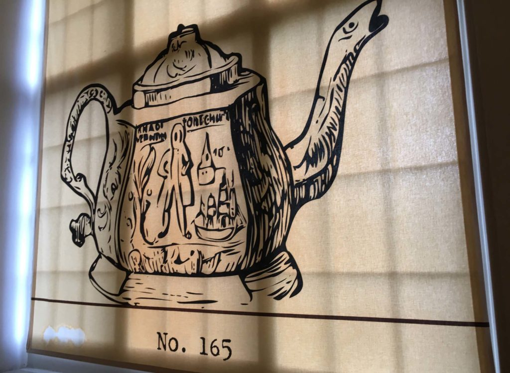 a photo of a window blind with a drawing of a teapot on it