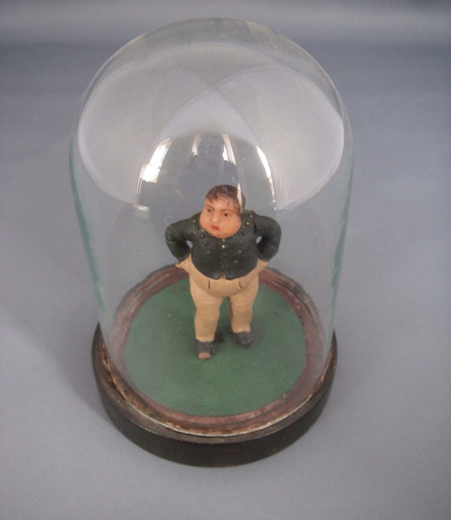 a photo of a clay figurine of a fat boy beneath a glass display dome