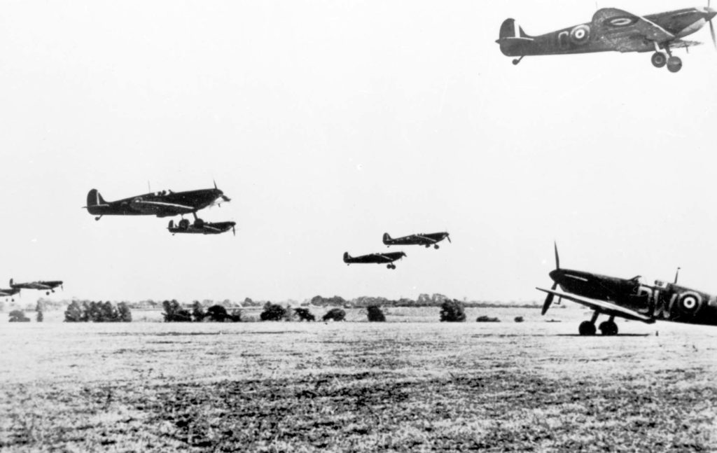 a black and white photo of a mass of Spitfires taking off from a grass runway