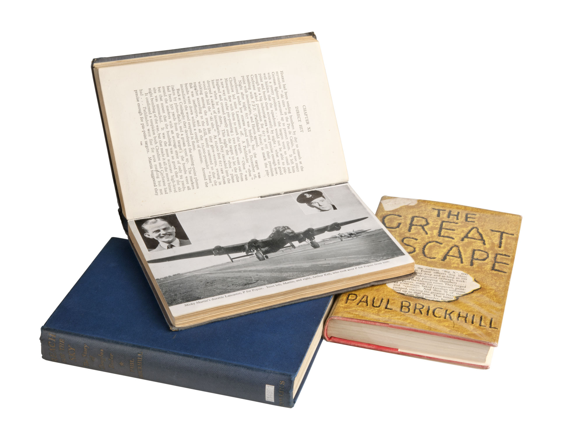 photograph of three books: 'Reach for the sky' and 'the great escape lay flat while a third book sits on top of them open to a page showing a photograph of an aircraft
