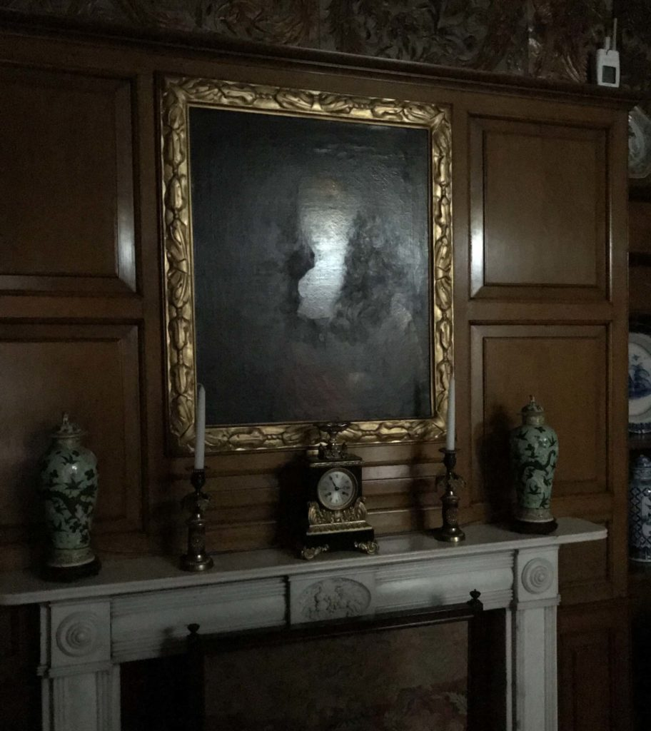 a photo of a portrait above a fireplace