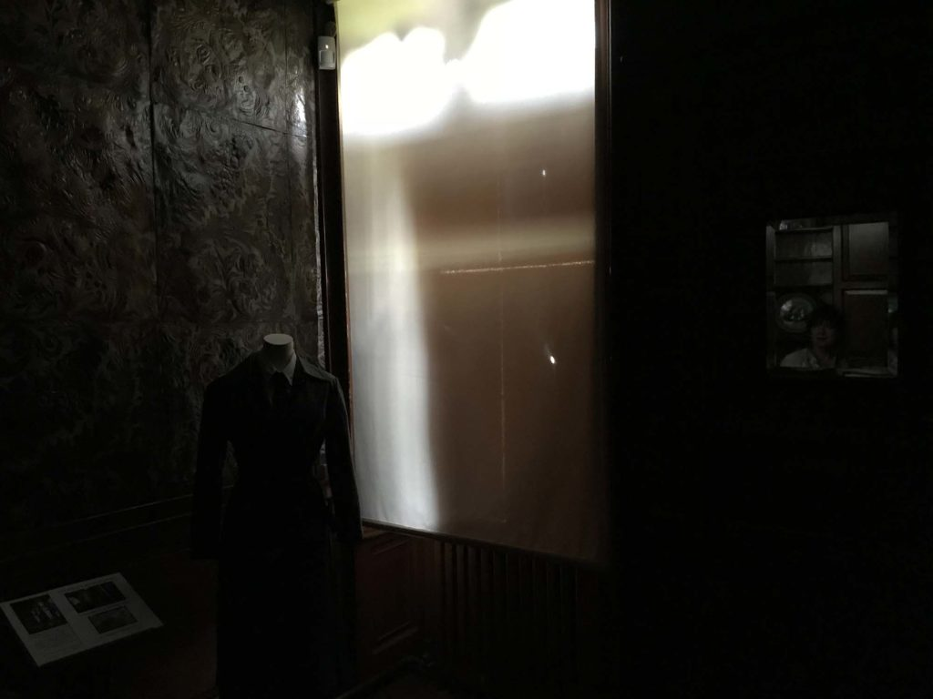 a photo of the corner of a darkened room with blinds and shutters