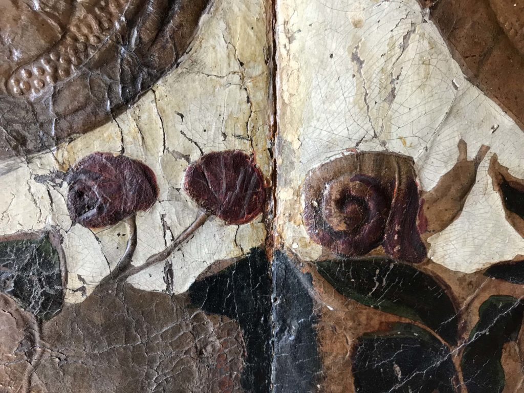 a photo of a detail of old wallpaper with snail and two berries
