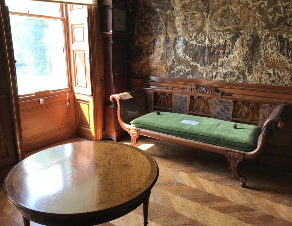 a photnof a corner of a room seen across a round table towards a shuttered window and sofa