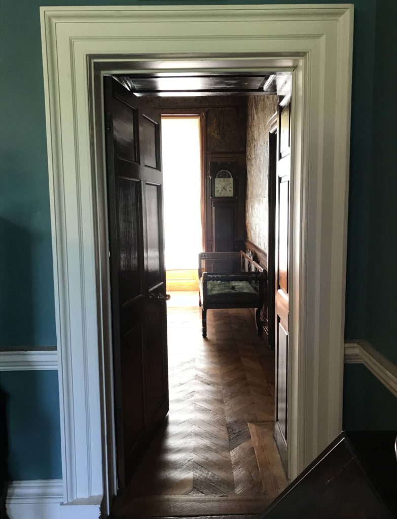 a photo of an interior doorway leading to a room with a sofa in it