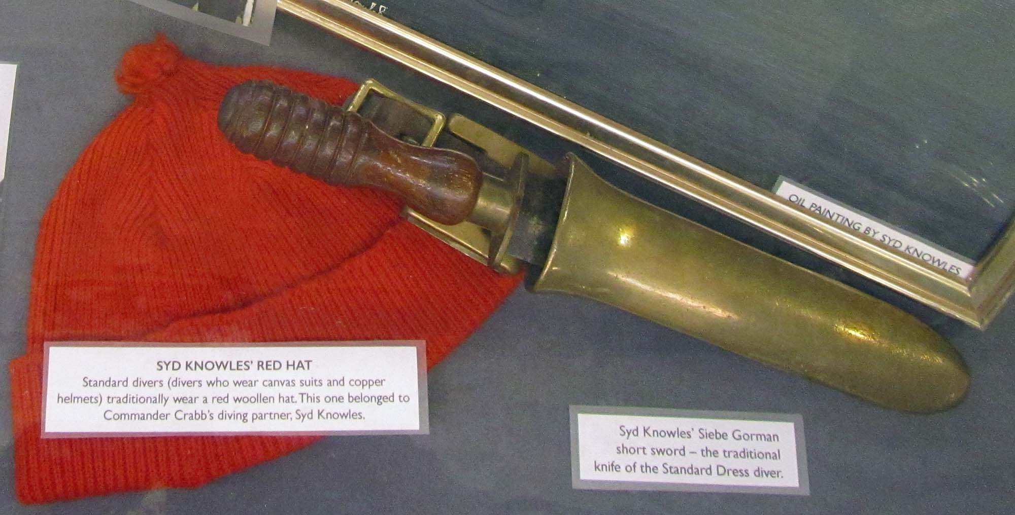 a photo of a knife and red woolly hat in a display case