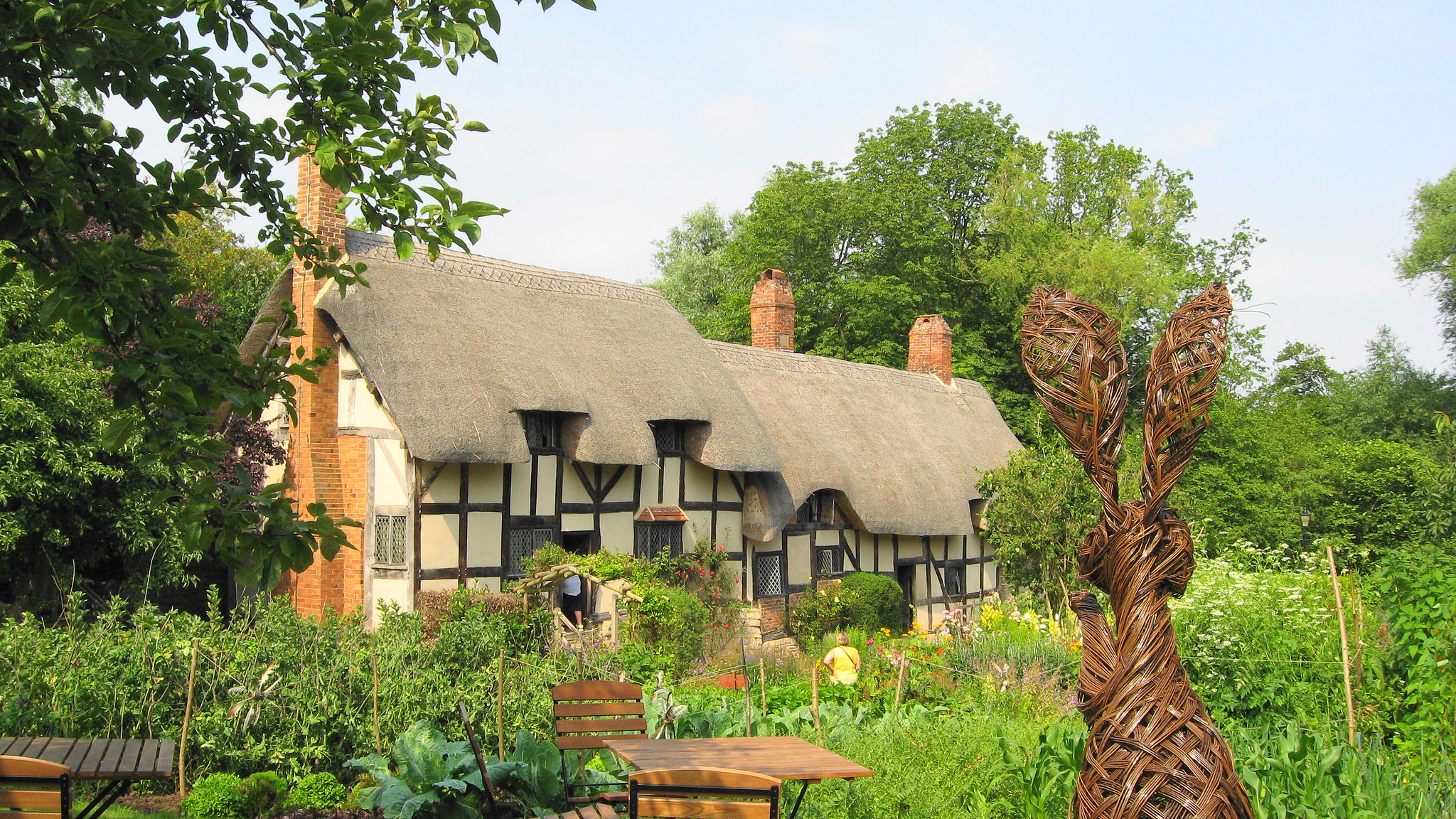 photograph fo exterior of large thatched cottage in cottage garden