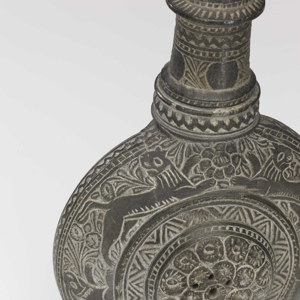 a photo of a an animal motif on the curve of a decorated stone bottle