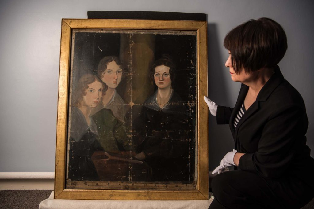 a photo of a person in white gloves looking at the Bronte sisters portrait in its gold frame
