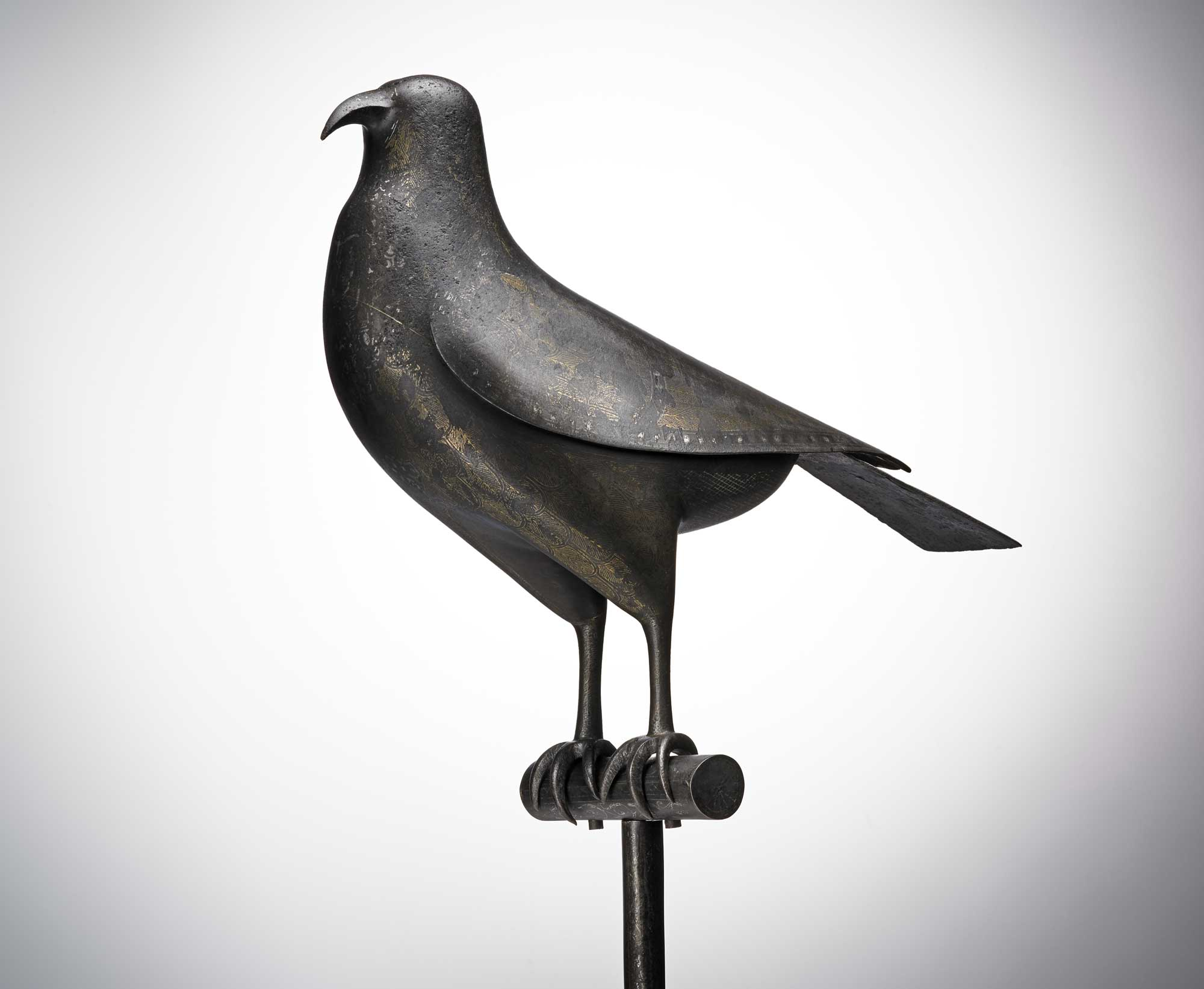 a photo of a metal bird inlaid with decoration