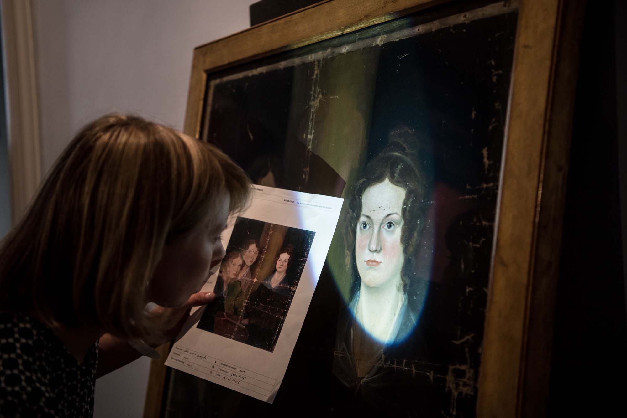 a photo of a woman staring closely at an illuminated portrait of Charlotte Bronte