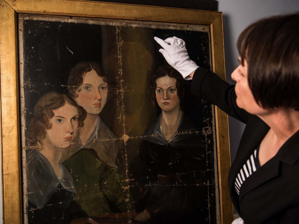 a photo of a woman with white gloves inspecting the group portrait of the Bronte sisters
