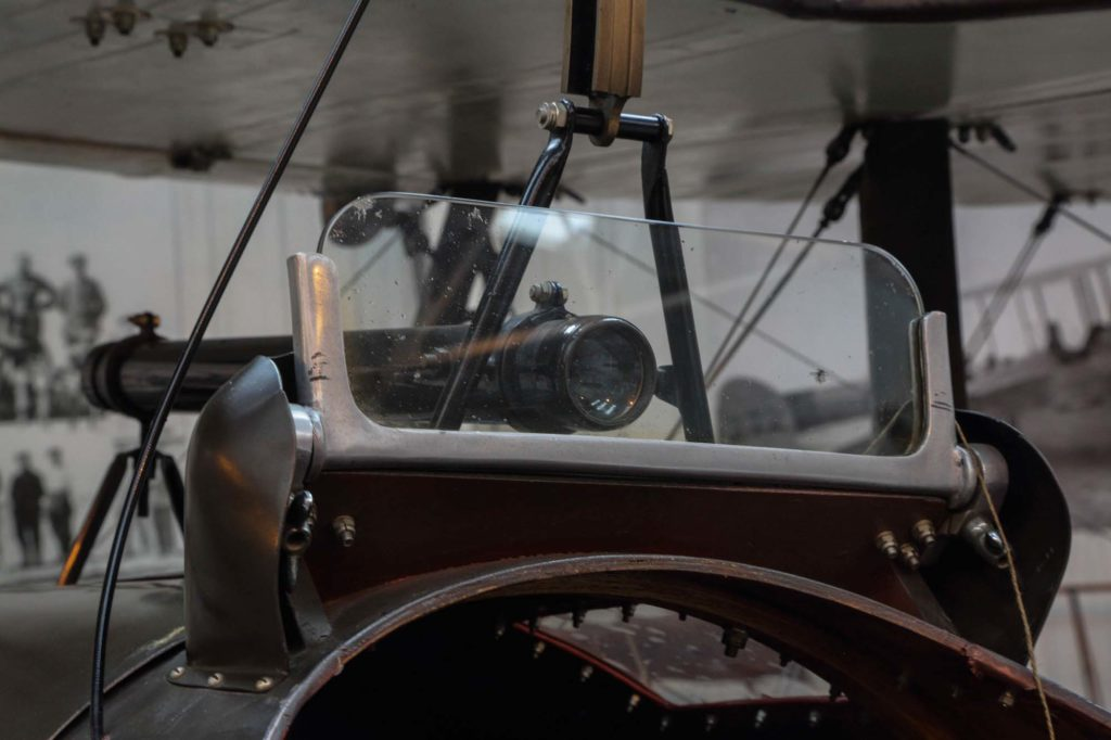 a photo lokking through the windshield of an old biplane with a gun site mounted on it