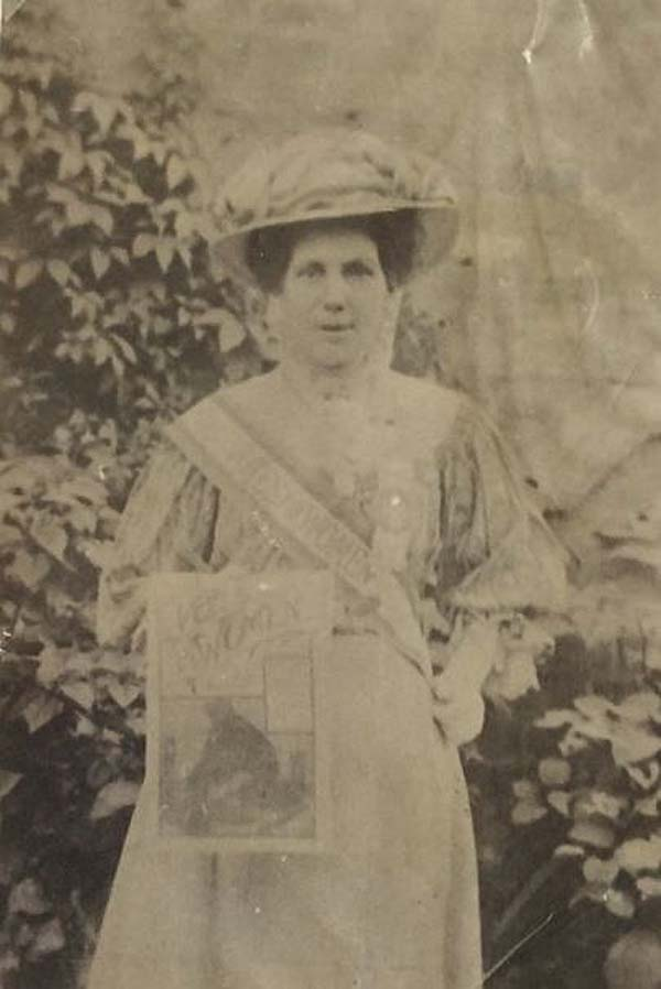 a black and white photo of a woman on period Edwardian dress
