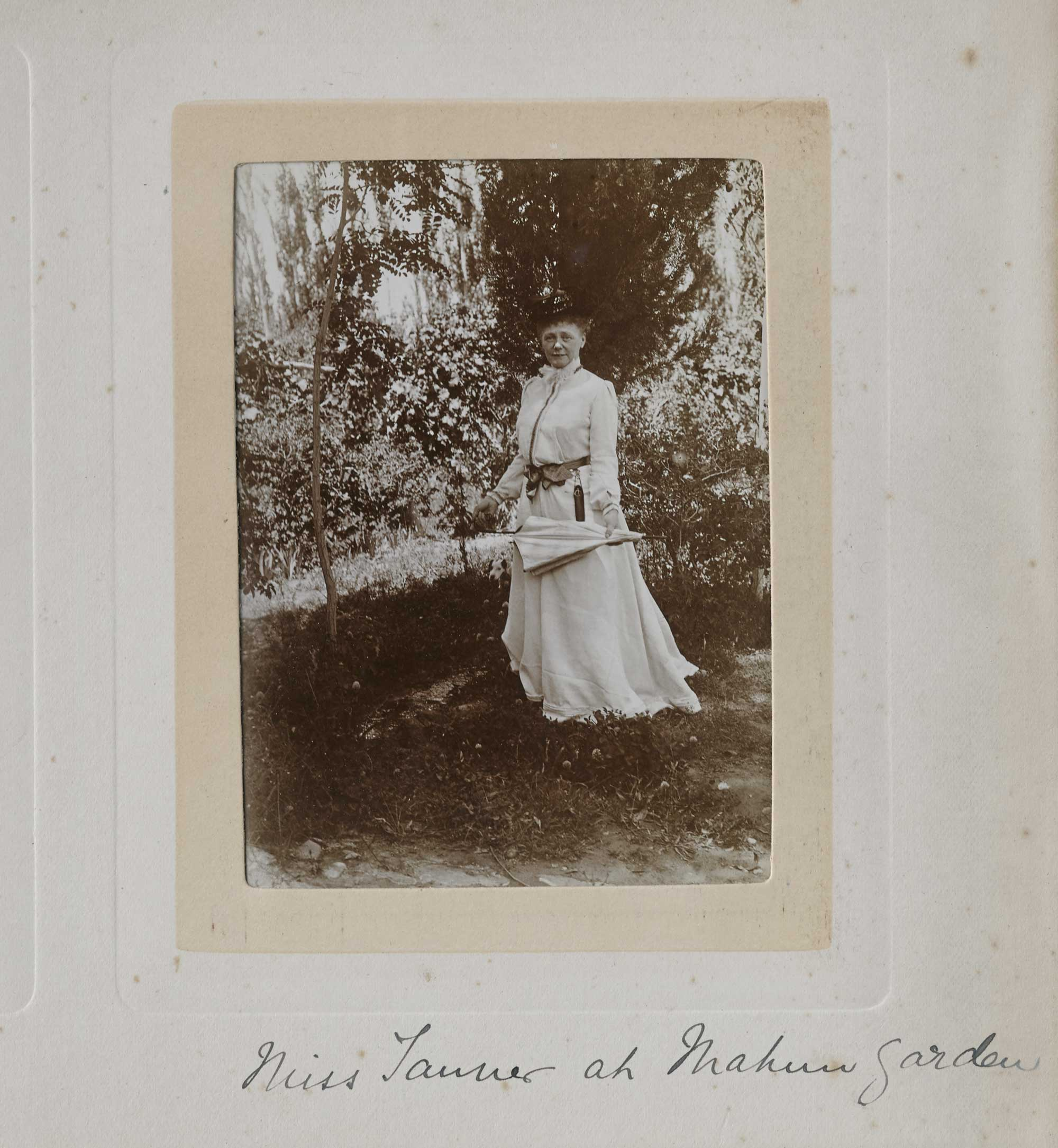 a photo of a woman in Victorian dress in a garden with a folded umbrella