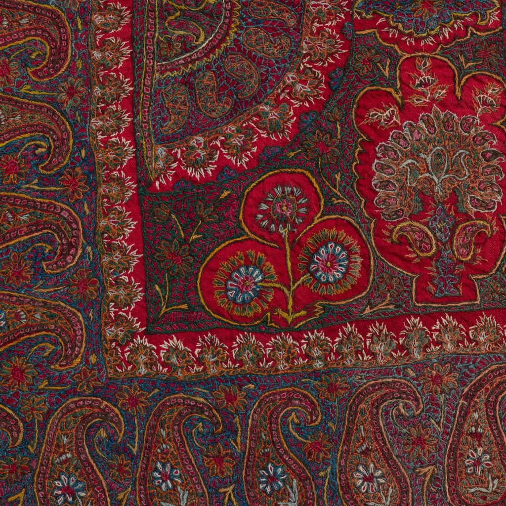 a detail of the decoration in purple and red of a Persian shawl