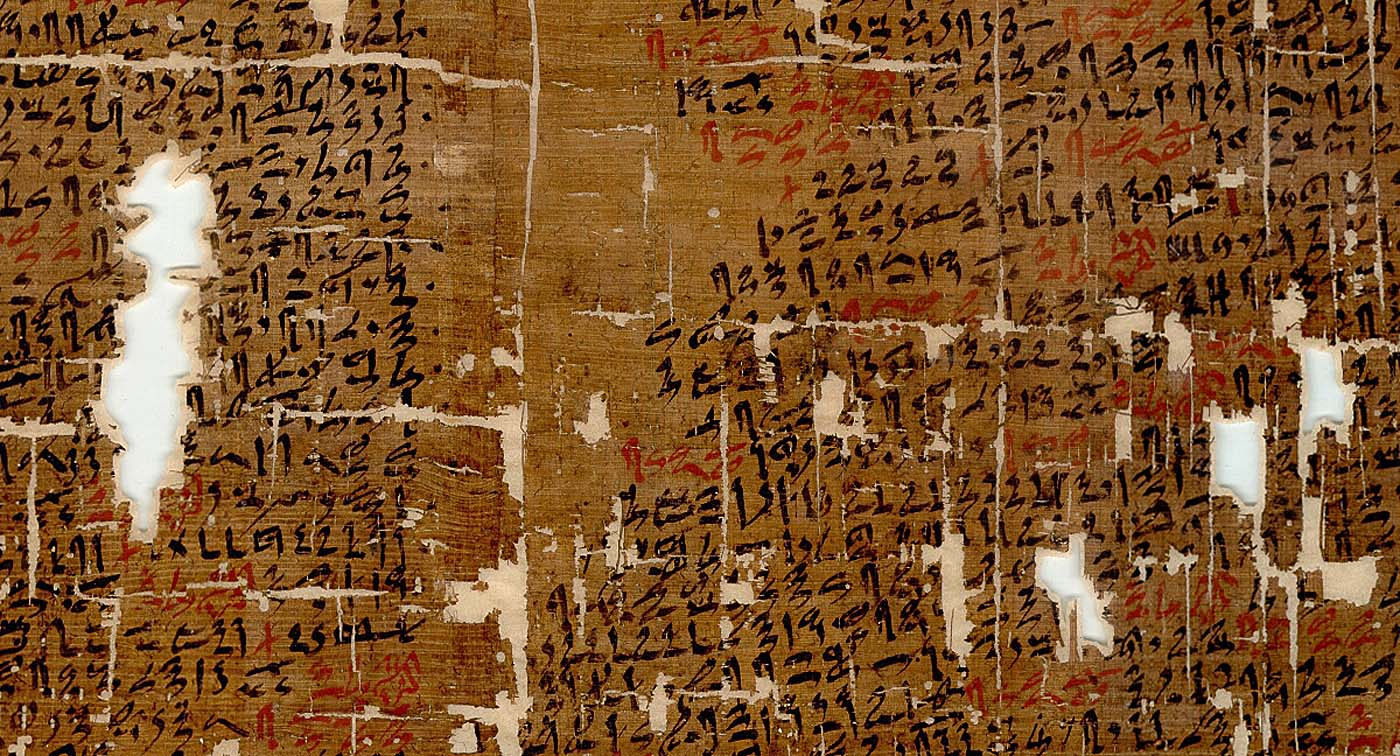 a close up of a papyrus with holes and Ancient Egyptian text on it