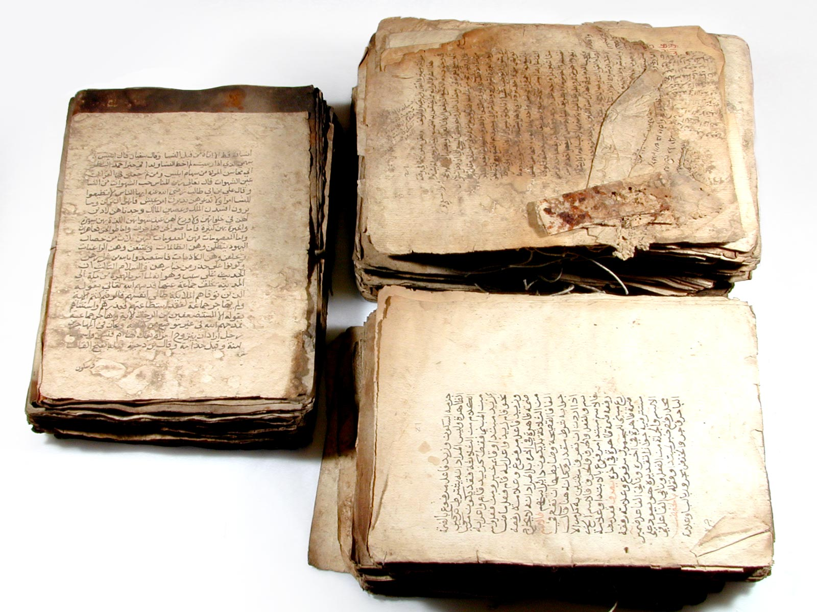 a photo of a three pages of an ancient text written in Arabic