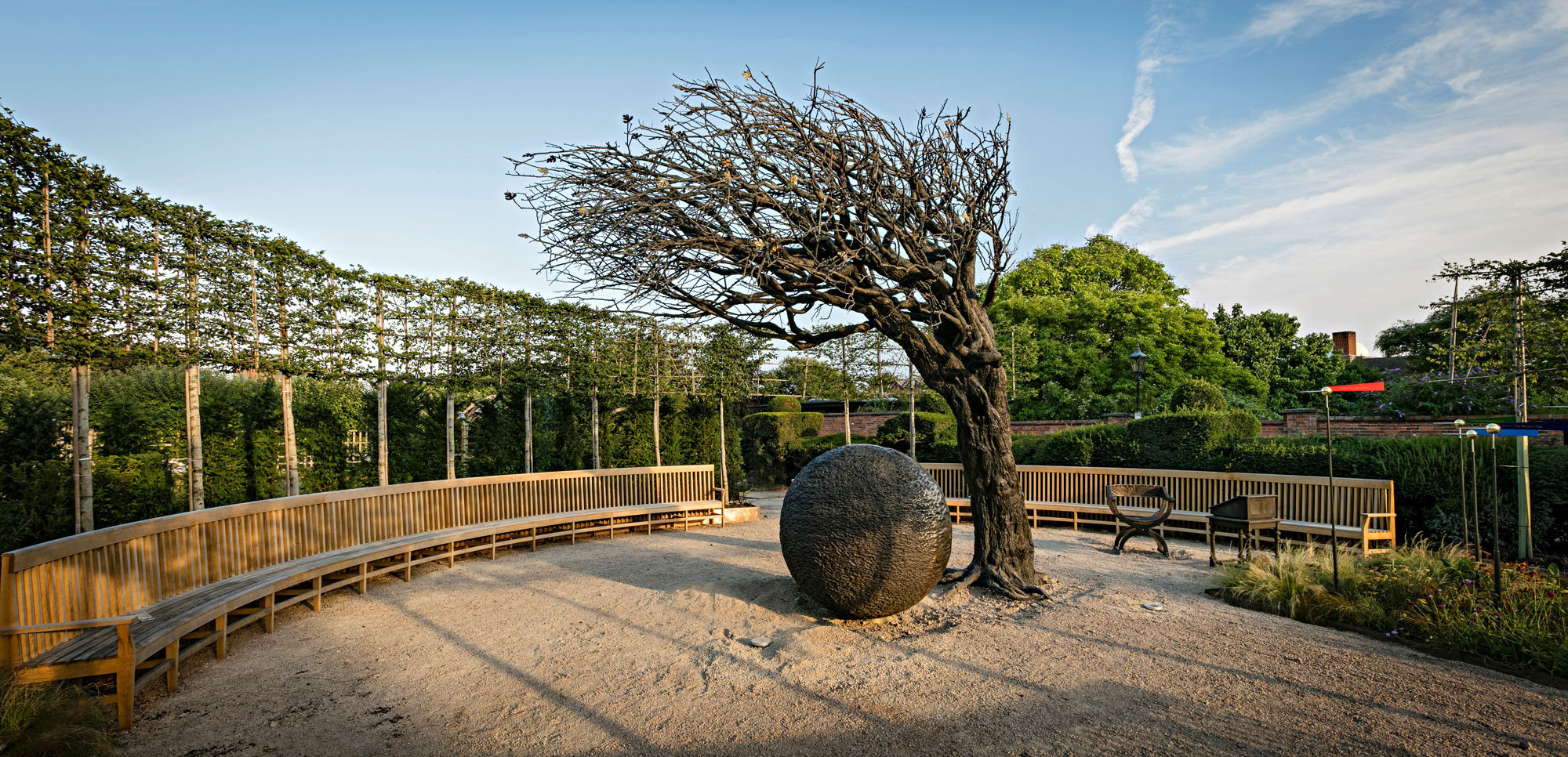 photograph of windswept tree and iron ball sculpture in garden