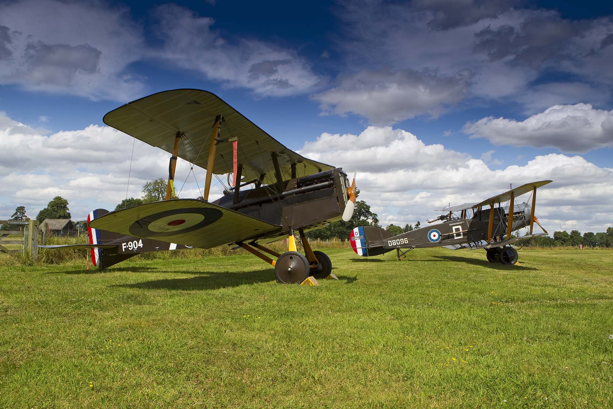 a photo of two biplanes lined up next to each other on a grassy airfield