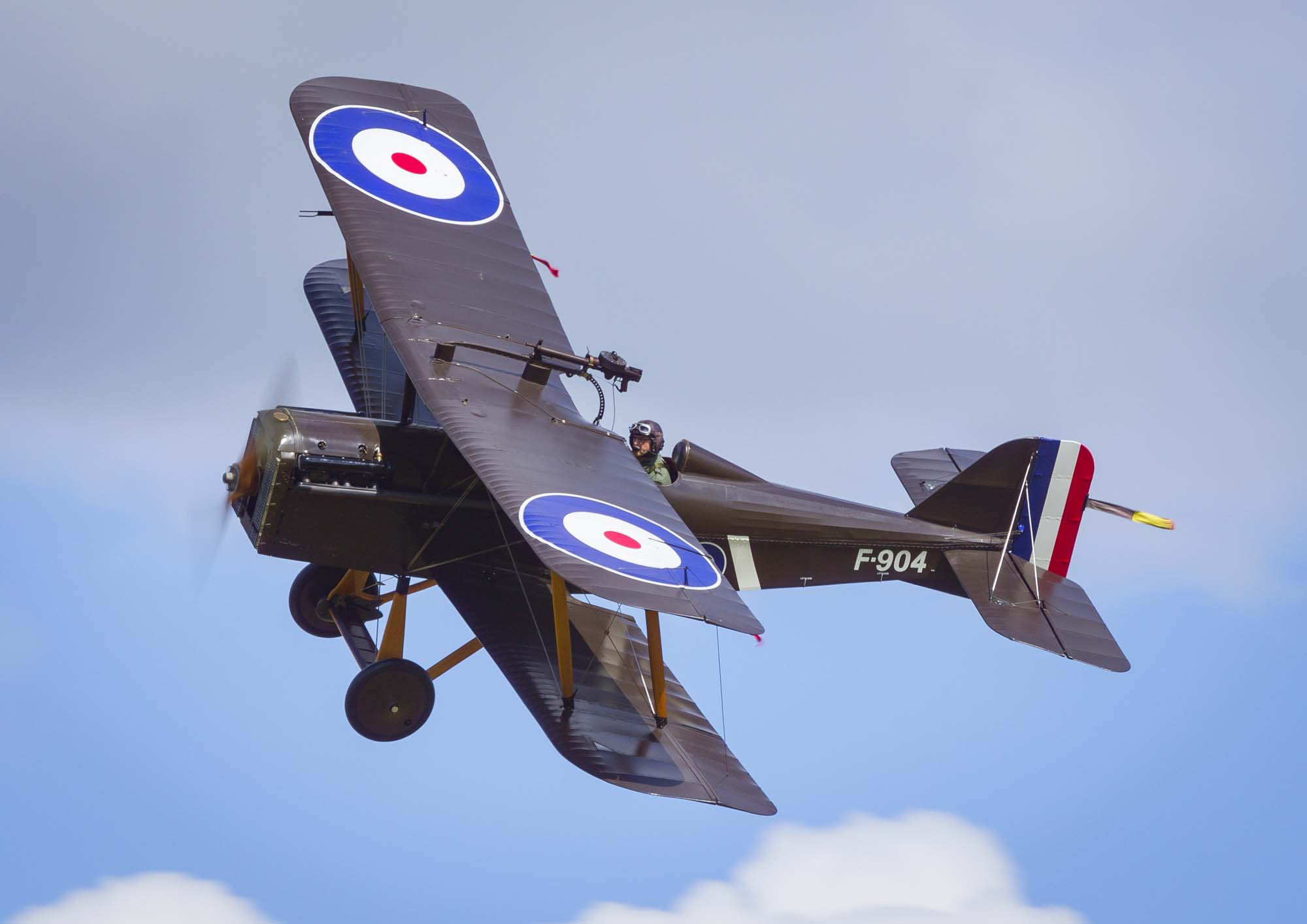 a photo of an RAF biplane with roundels flying across a blue sky with a few cotton clouds