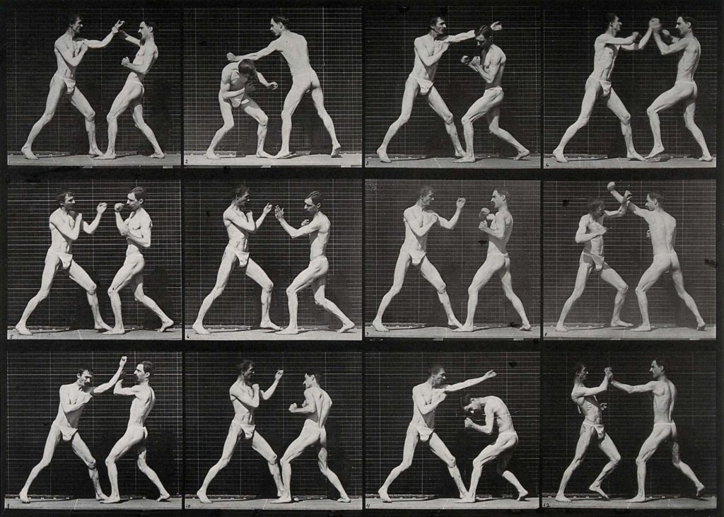 multiple frames of two men in loincloths boxing