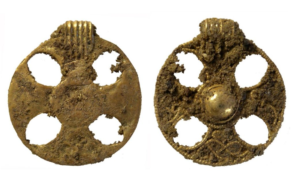 a photo of both sides of an uncleaned pendant with a cross decoration