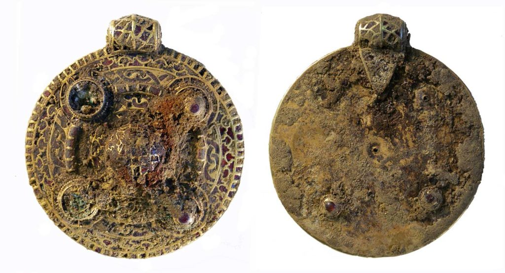 a photo of a round uncleaned golden pendant encrusted with garnets