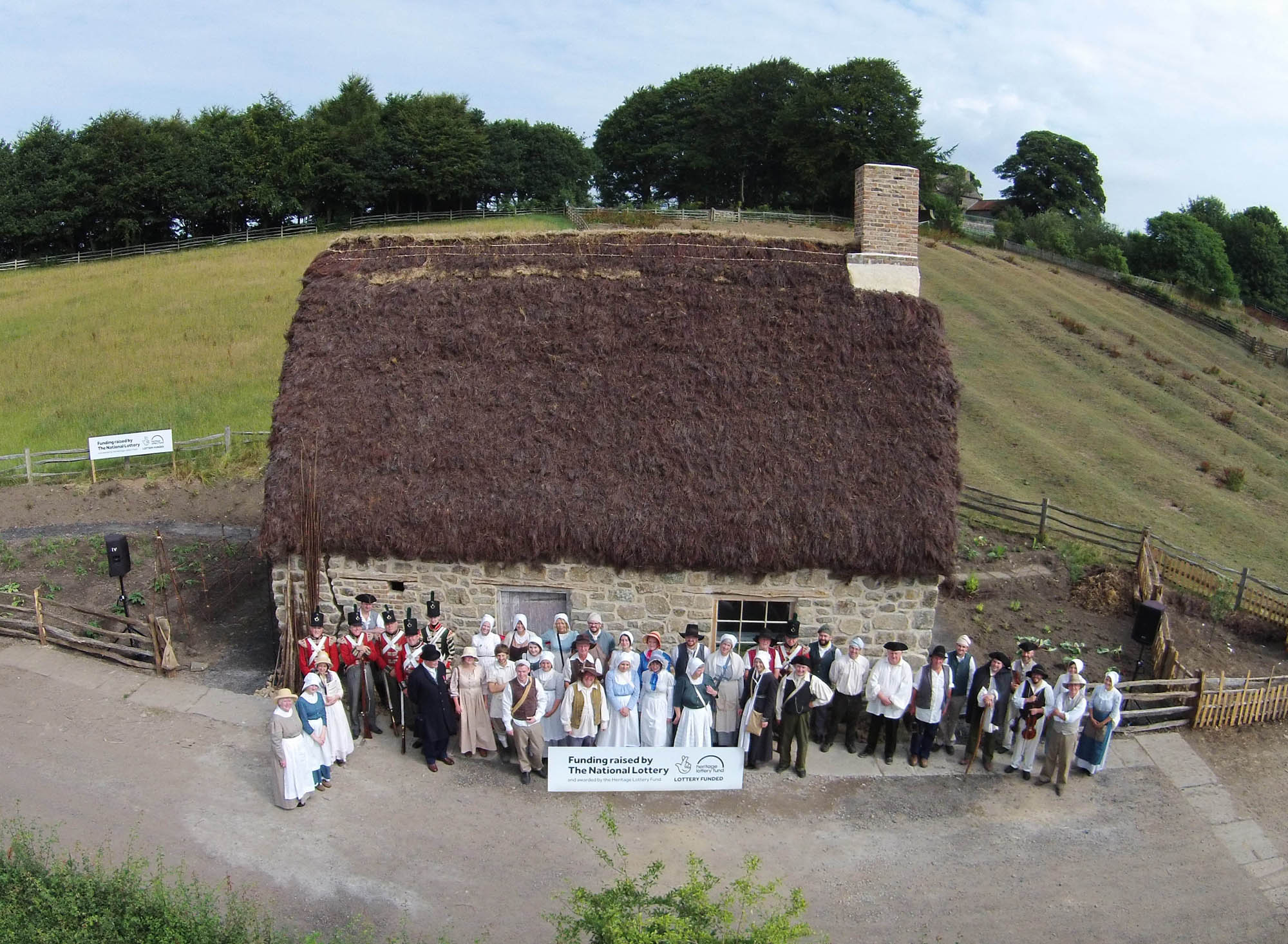 a photo of a thatched cottage with a group of people i Georgian dress outside it