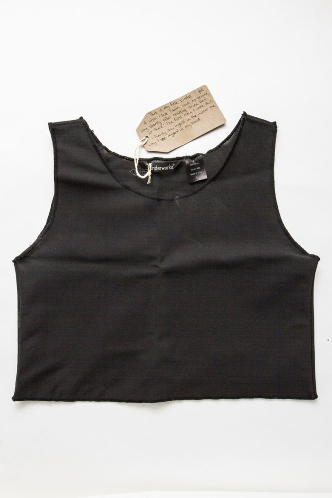 photograph of black undergarment used to bind chest with brown handwritten tag