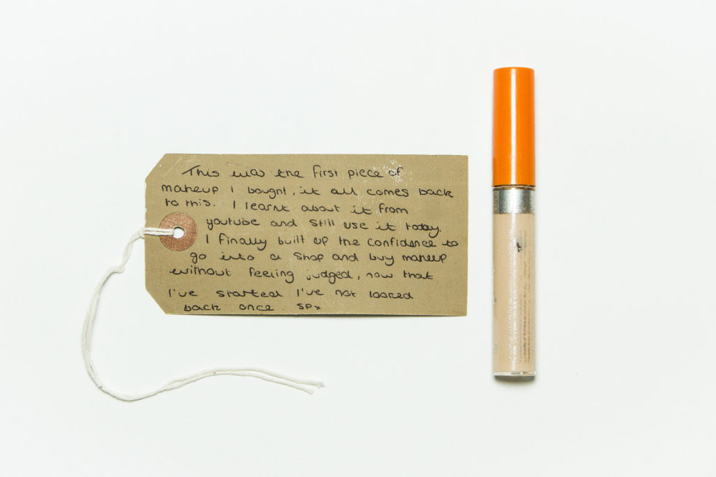 photograph of tube of concealer with orange lid and brown handwritten tag