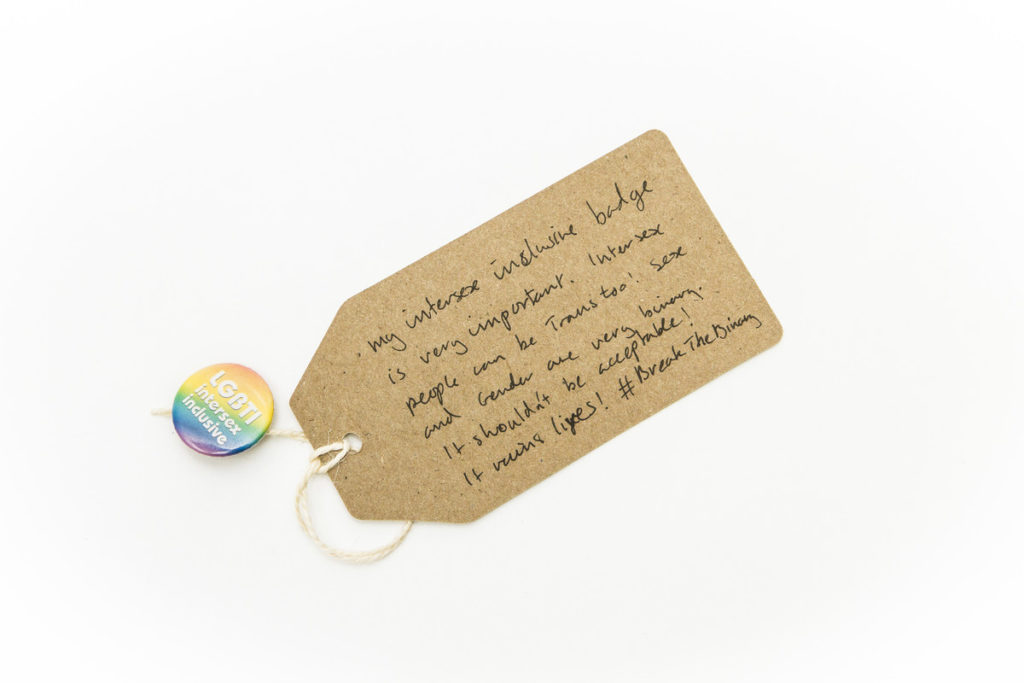 photograph of button badge with rainbow backgrouns and slogan 'LGBTI intersex inclusive' with brown handwritten tag