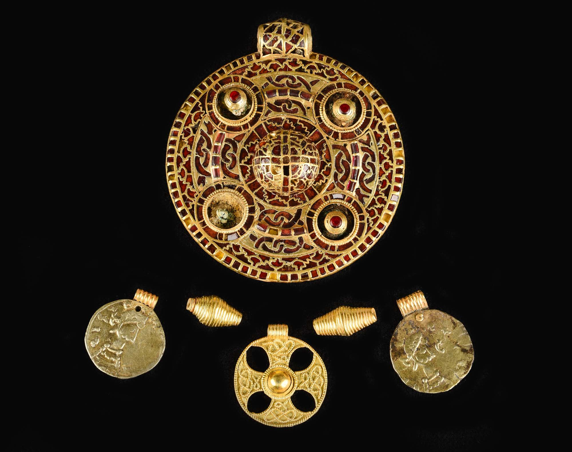 a photo of a large round gold pendant encrsuted with stones together with three smaller gold pedants and two conical gold spacers