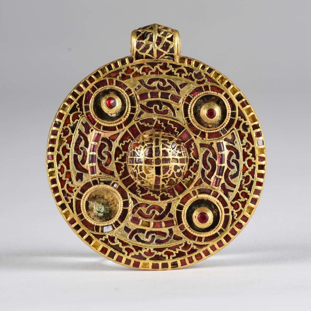 a photo of a round golden pendant encrusted with garnets