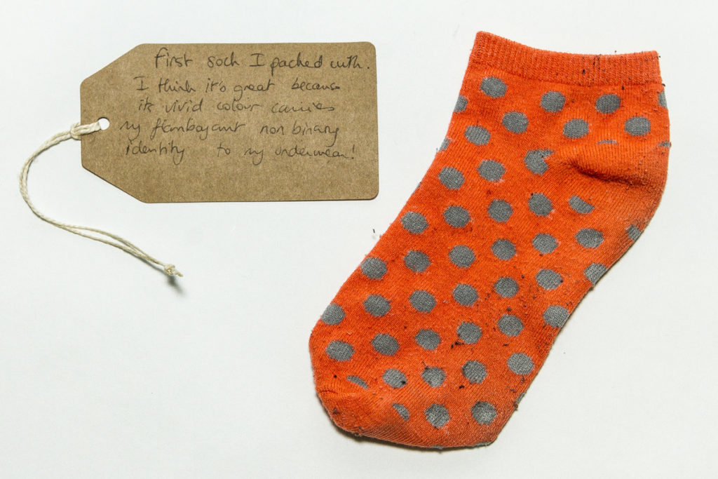 photograph of orange and green spotted sock with brown handwritten tag